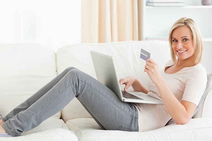 Cute woman buying on line while lying on a couch looking at the camera.jpeg