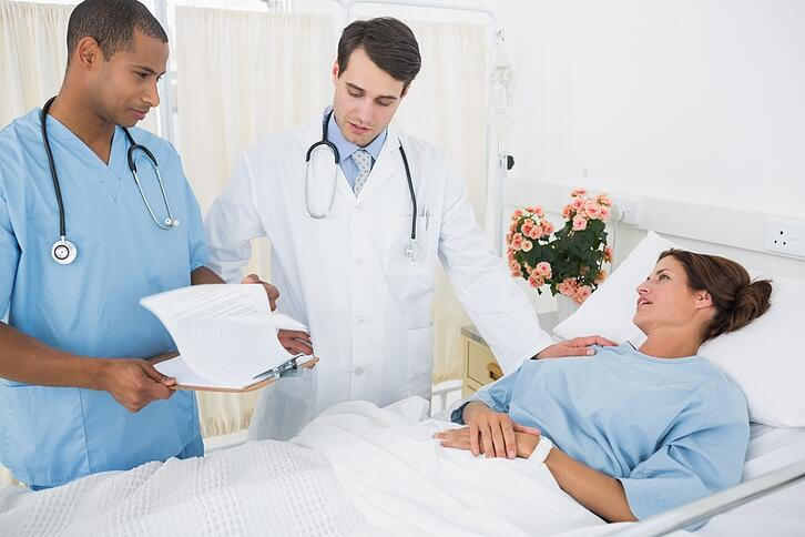 Doctor and surgeon visiting female patient in the hospital.jpeg