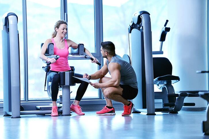 Gym woman exercising with her personal trainer.jpeg