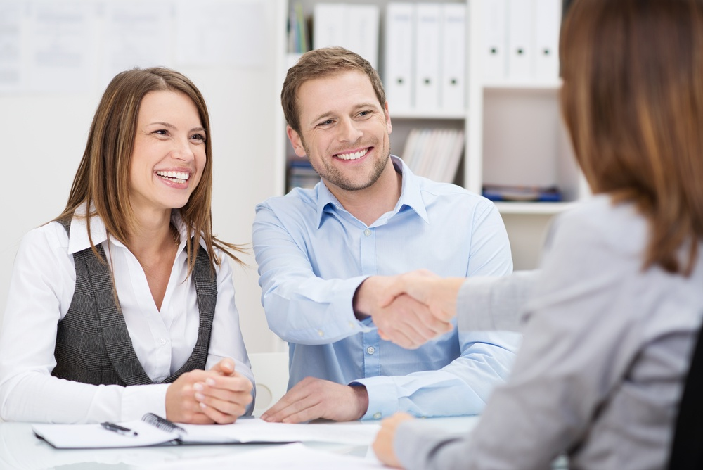 Smiling young man shaking hands with an insurance agent or investment adviser as he sits in a meeting with his wife in her office.jpeg