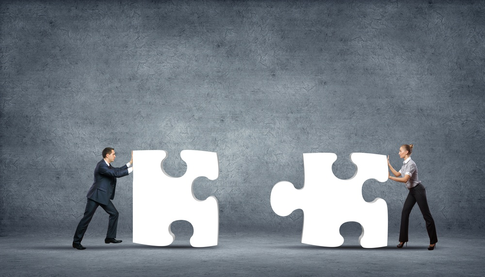 Team of business people collaborate holding up jigsaw puzzle pieces as a solution to a problem.jpeg