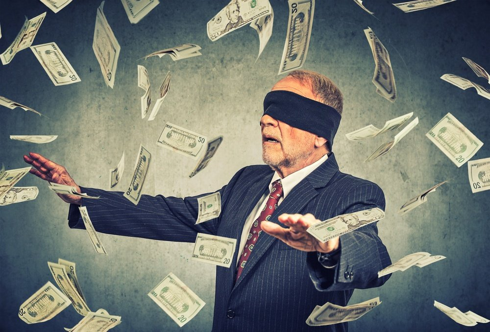 Blindfolded senior businessman trying to catch dollar bills banknotes flying in the air on gray wall background. Financial corporate success or crisis challenge concept  .jpeg