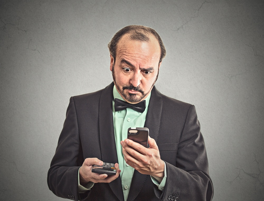 Portrait surprised businessman looking on smart phone holding calculator unexpected financial bills charges isolated grey wall background. Human face expression, emotion, body language, reaction