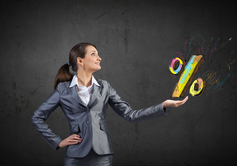 Young businesswoman holding percentage symbol in palm